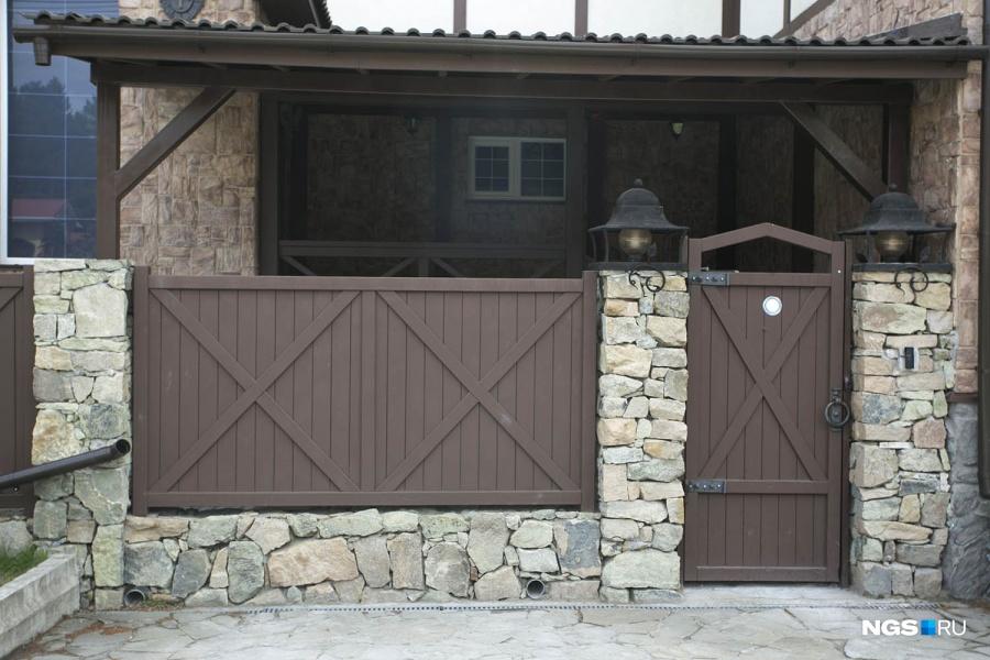 У владельцев дорогих коттеджей больше возможностей сделать забор со вкусом — например, здесь собственник поддержал фахверковый стиль дома.