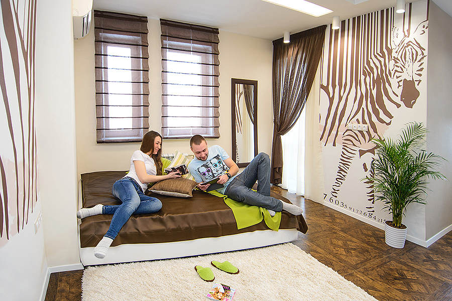 Спальня пронизана солнечным светом — в ней четыре окна и балкон с панорамным видом на «Ауру». Фотообои «зебра» и спальный гарнитур выполнены по индивидуальному заказу.