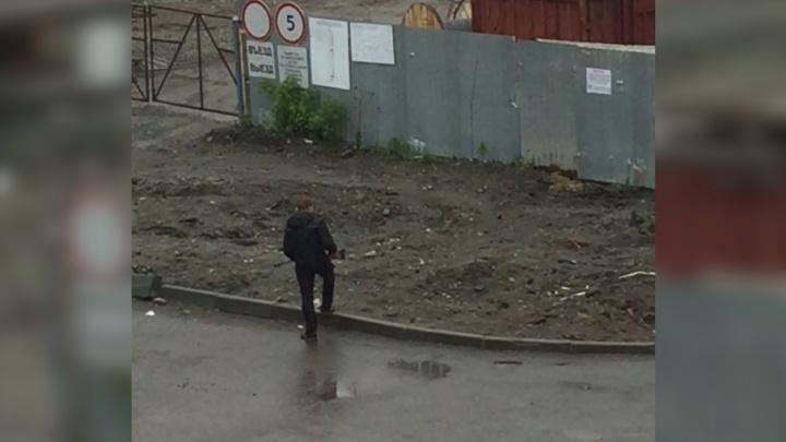 «Кого-то искал»: в Челябинске сняли на видео мужчину, разгуливавшего во дворе с ружьём