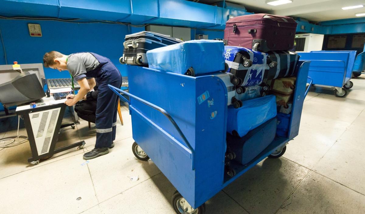 Багаж, который сдали пассажиры, сортируется и отправляется к борту