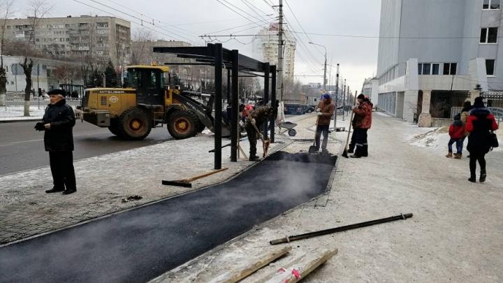 Лёгкий мороз и снег не мешают рабочим класть асфальт на улице Невской