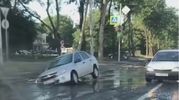 Автомобиль провалился колесами в дыру в асфальте на ул. 1-й Конной Армии