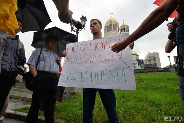 Молодой человек несколько минут постоял под дождём с плакатом.