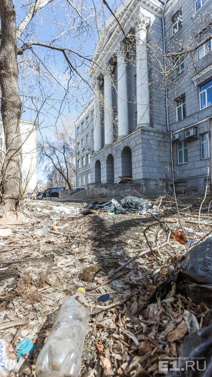 Рядом валяется мусор, и на главный вход это нисколько не похоже. Студенты, которые используют территорию за зданием в качестве курилки, увидев камеры, разбежались.