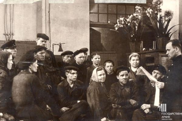 Агитатор Мосягин читает газету группе работников депо Пермь-II, 1954 г. Молотов