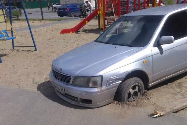 Автомобиль, забуксовавший на детской площадке, застрял передними колёсами в песке