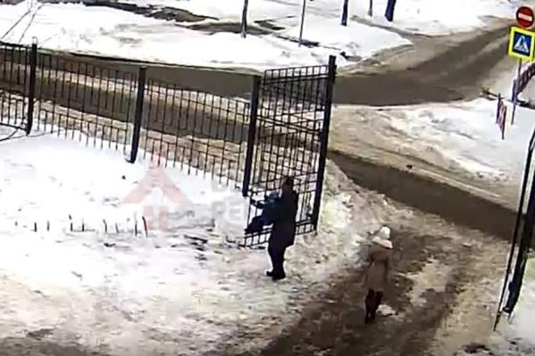 Женщина качала на воротах ребенка