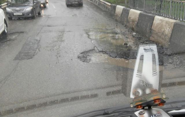 На Западном дождь смыл асфальт на мосту через Темерник