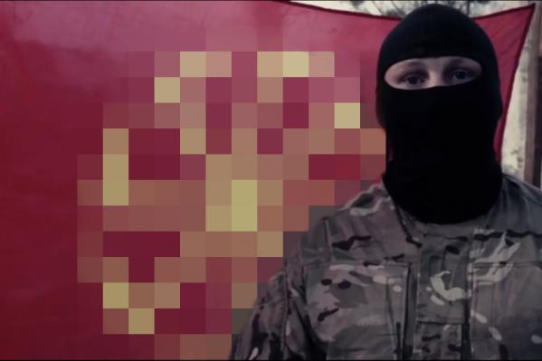 Неизвестный человек в камуфляже на фоне флага с неонацистской символикой