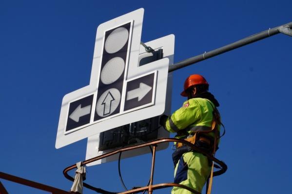 Монтажник закрепляет конструкцию на опоре по проспекту Кирова