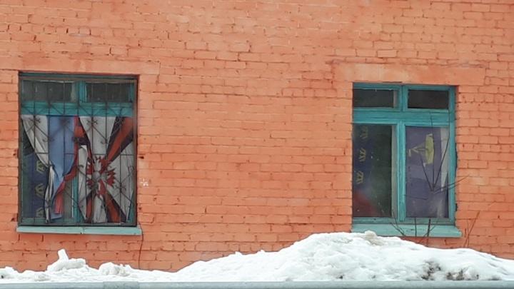 Окна двухэтажного здания, которое принадлежит администрации, завесили флагами России и Тюменской области