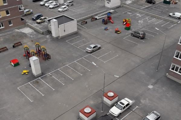 Разметка для парковки автомобилей находится в паре метров от детских площадок