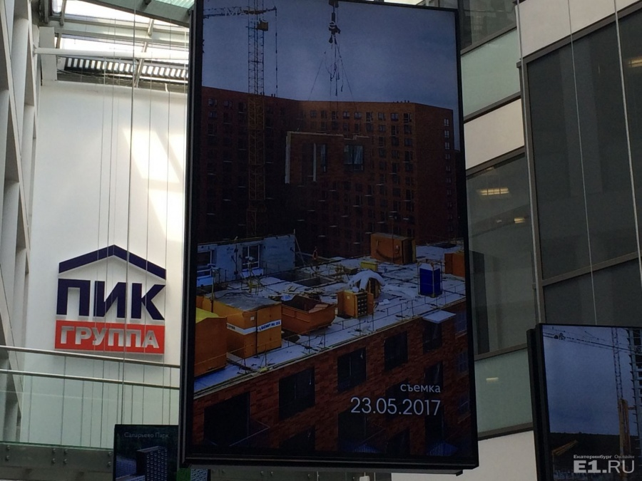 В центральном холле главного офиса висят экраны, демонстрирующие, как идет строительство того или иного комплекса. Вот тут, например, видно, как панель – с плиткой и остеклением – кран несёт по воздуху.