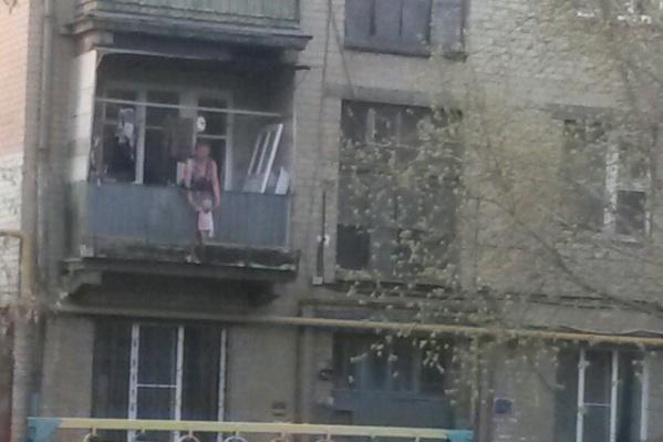 Женщина выгуливала ребёнка, держа за ручки за ограждением балкона