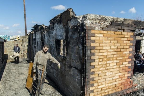 Рабочие убирают территорию , где случился пожар