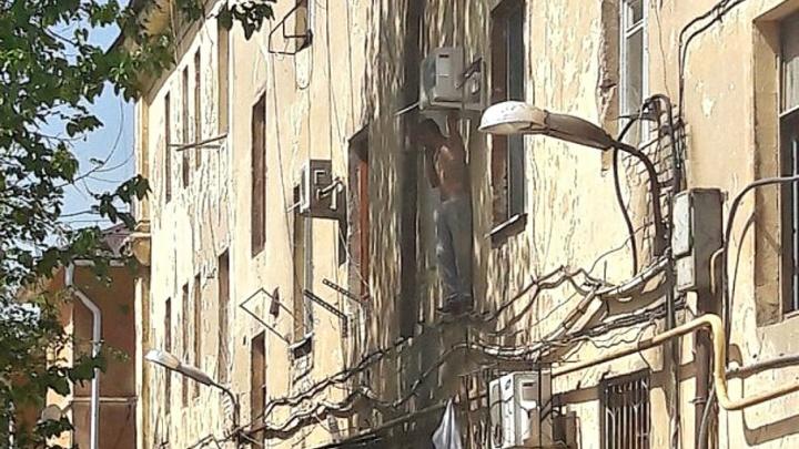 В Волгограде второй час пытаются снять с окна мужчину