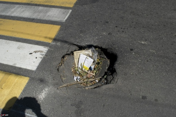 Автомобилисты стали засыпать яму мусором