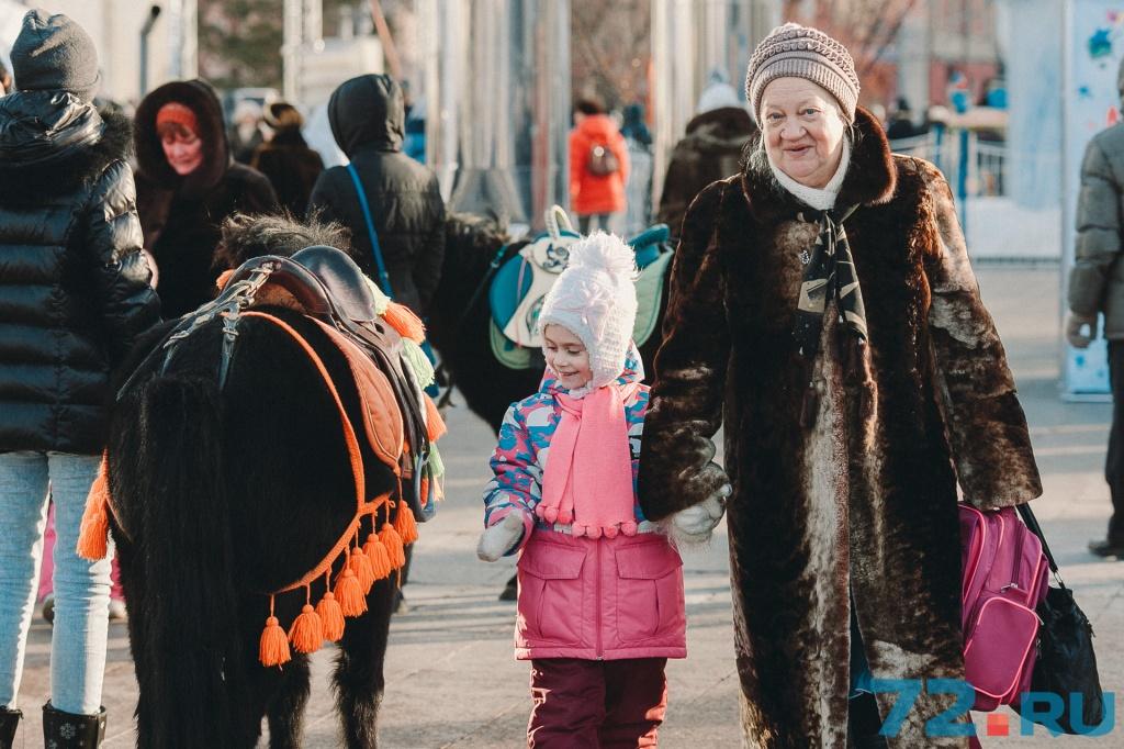 Пока внучка разглядывает мини-лошадку, синеглазая тюменка позирует нашему фотографу как настоящая модель