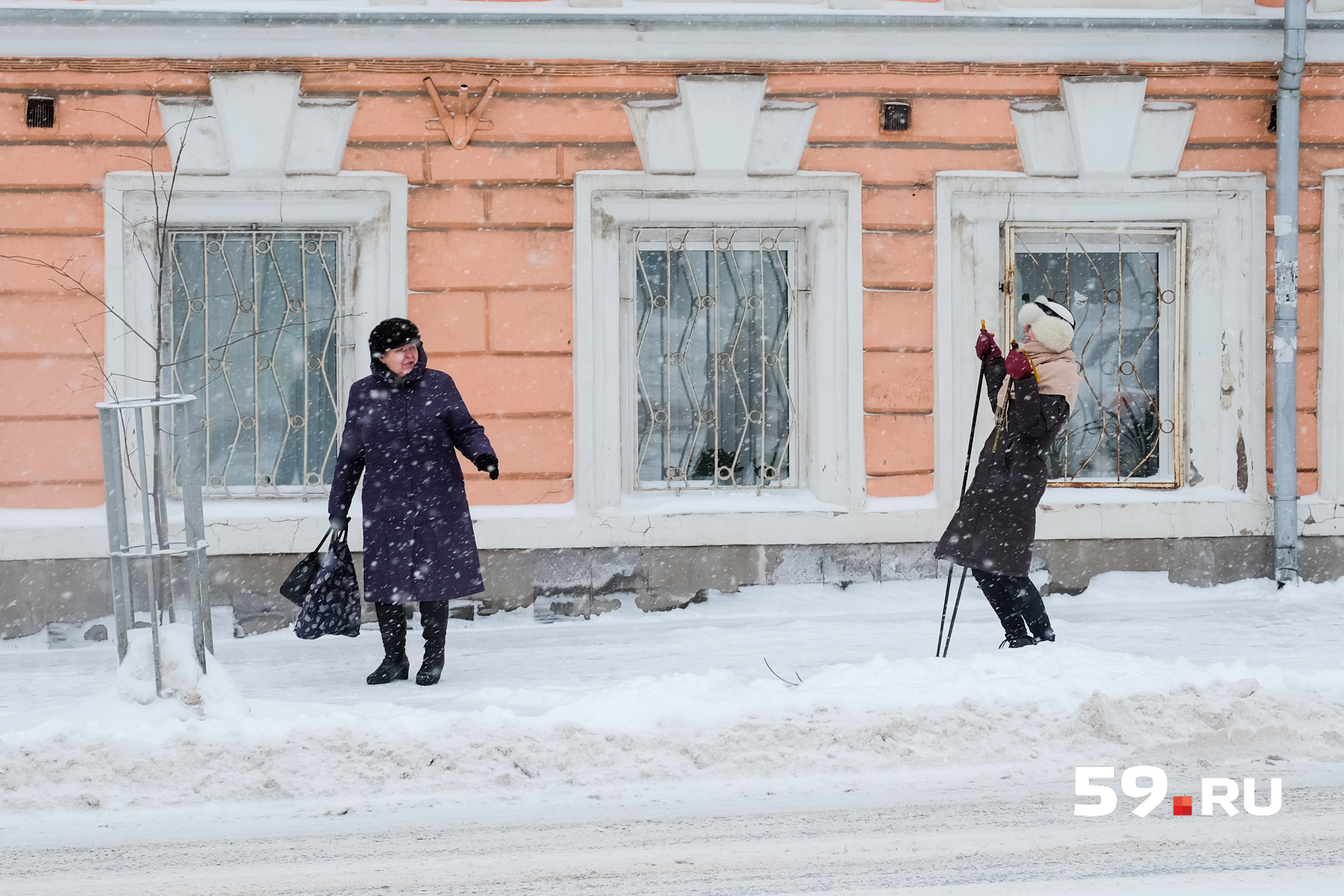 Прохожие, вынырнув из своих шарфов, удивляются лыжнику в центре города