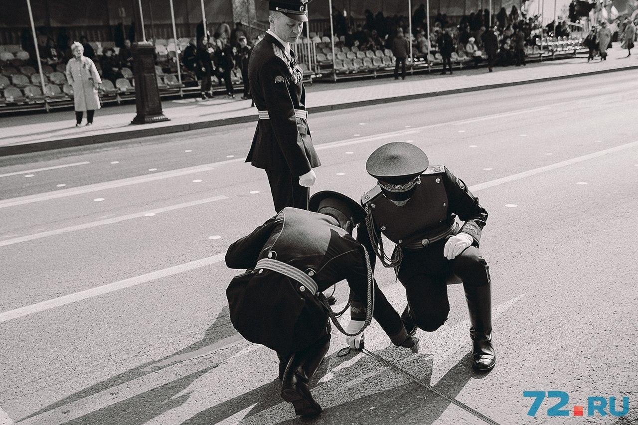 Участники парада делают отметки мелом на асфальте, чтобы легче было ориентироваться в ответственный момент