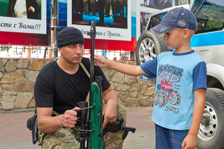 Ребетня с интересом разглядывала оружие. Но только из рук военных