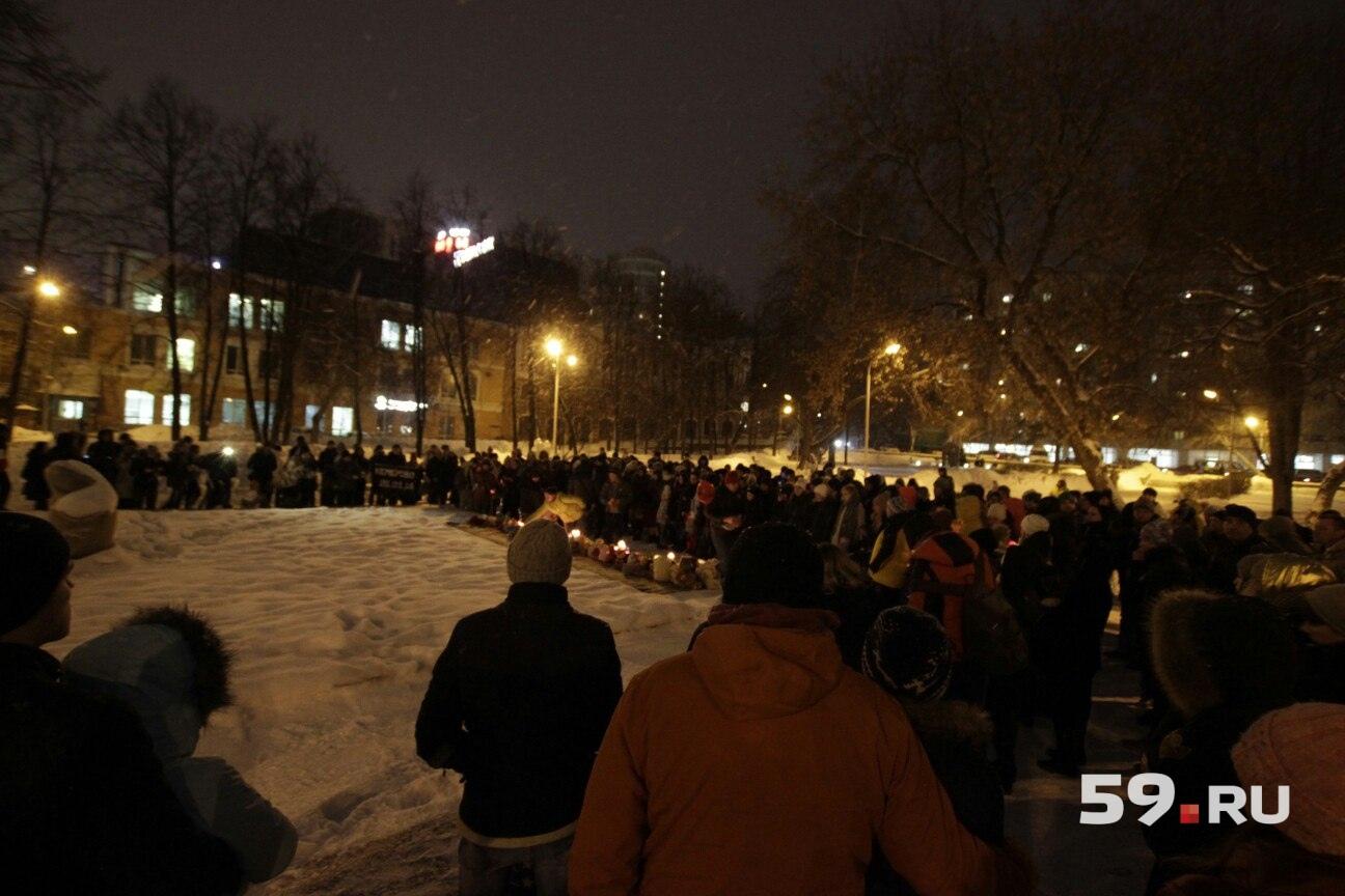 Люди окружили мемориал полукругом