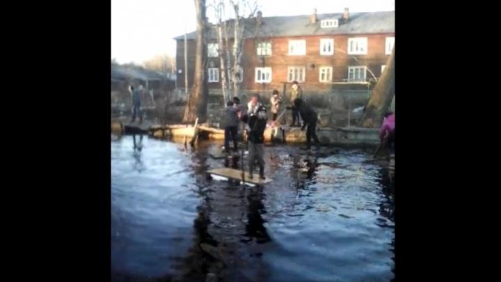 Перебираются на плотах: на 14-м лесозаводе дети устроили плавание в огромной луже