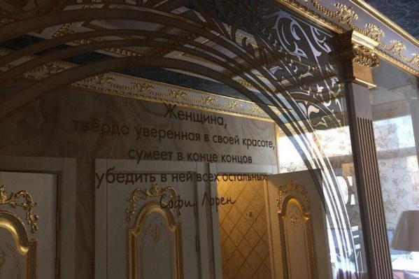 На зеркале в туалете цитаты Софи Лорен, написанные золотой краской