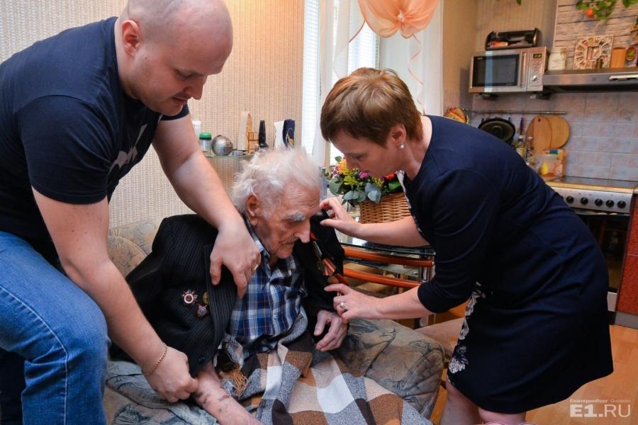 Родные помогают надеть парадный пиджак с медалями и орденами.
