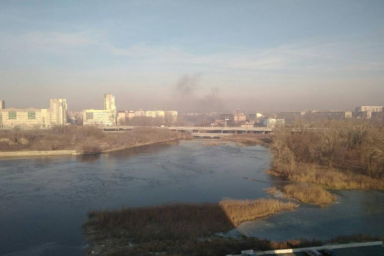 Над рекой четко видно черный дым
