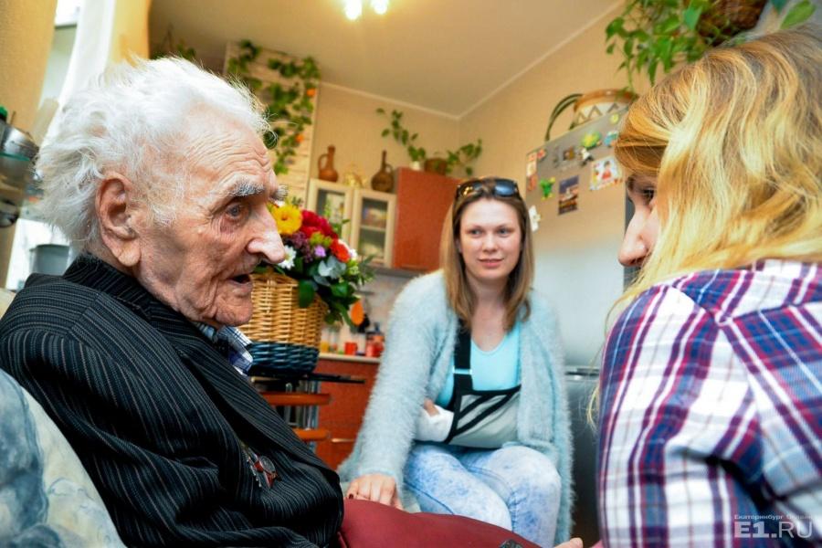 За руку Александра Герасимовича держит жена его внука Юлия. Девушка рассказала, что дочка ветерана записывала его воспоминания в тетрадку, и она их иногда читает.