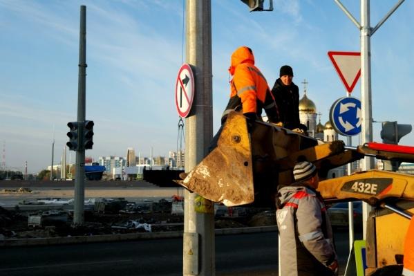 Рабочие установили дорожный знак на съезде с кольца