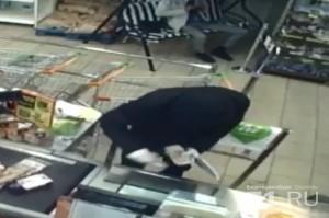 Грабитель оттолкнул кассира и стал спокойно набирать себе деньги из кассы.