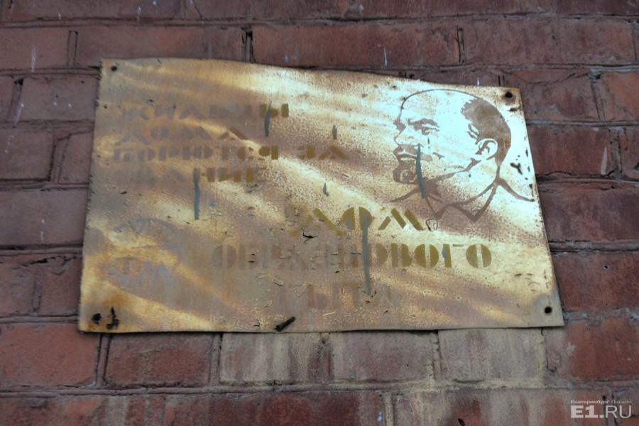 """По соседству с директорским домом стоит кирпичный – вот с такой доской. Под краской ещё можно прочитать надпись: """"Жильцы дома борются за звание """"Дом образцового быта"""""""