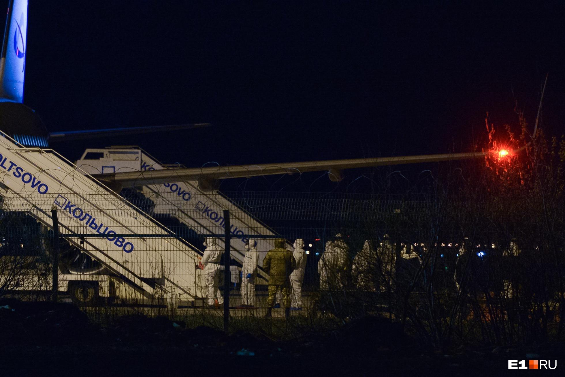 Люди в защитных костюмах ждали пассажиров у трапа