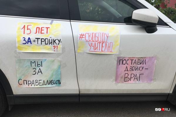 Перед судом на импровизированный пикет вышли выпускники школы, но после того, как к ним подошла полиция, плакаты пришлось повесить на автомобиль