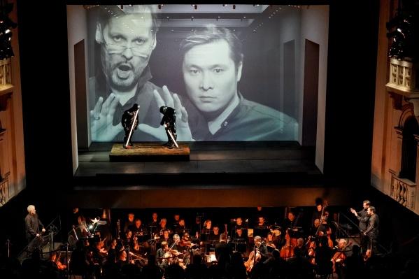 Во время спектакля на экране показывают лица солистов. Но это не запись, а прямая трансляция. Смотрите внимательней — артисты находятся в оркестровой яме
