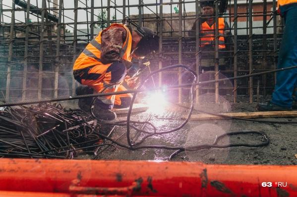 Рабочие возводят конструкцию из арматуры