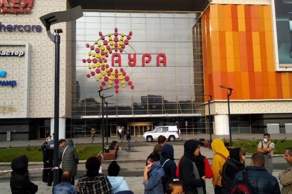 Небольшая толпа людей стоит у здания ТРЦ