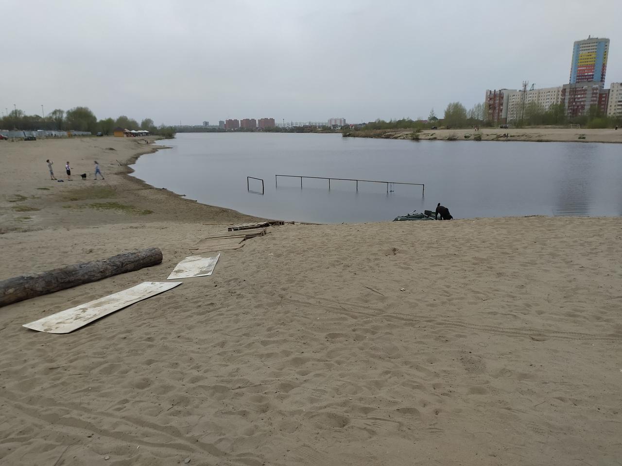 У озера гуляют только небольшая группа людей и одинокая собака