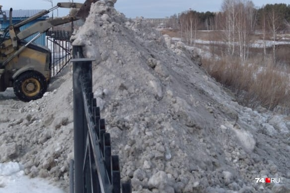 Снег сгребли с территории элитного посёлка на отвесный берег реки