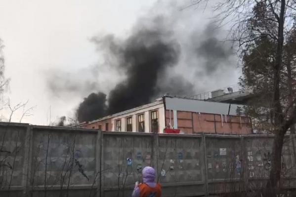 Дым, по словам очевидцев, идет из-под крыши старого здания