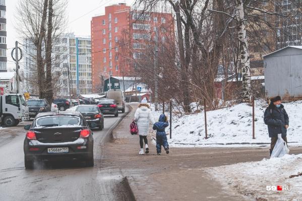 Люди ходят по тротуару, но пропускают машины, чтобы перейти дорогу