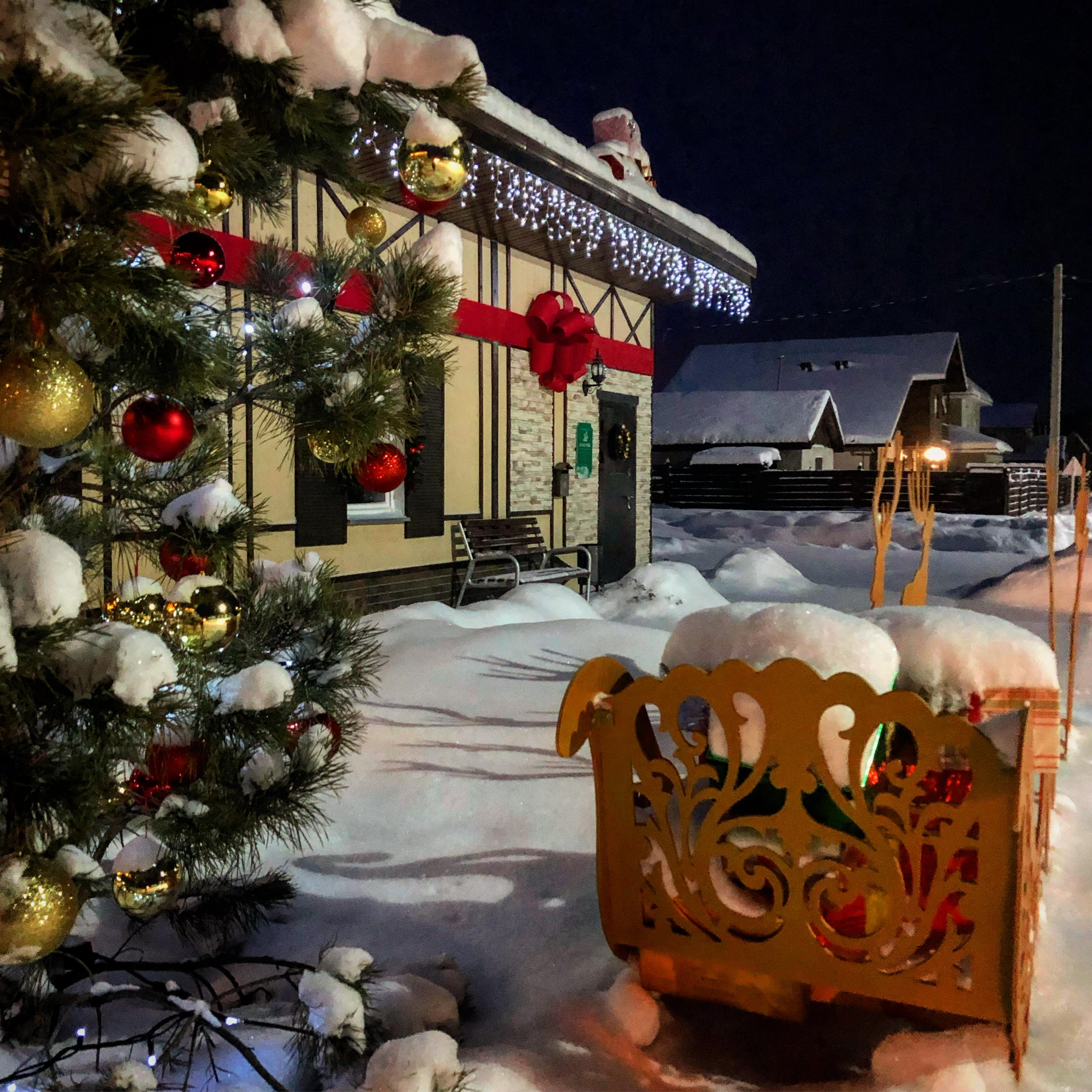 Гирлянды, ленты, шарики и даже новогодние сани — владельцы коттеджа постарались вовсю, чтобы создать волшебство у себя во дворике