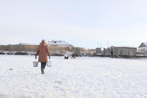 Жители поселка Чебаки ходят за водой на скованный льдом пруд