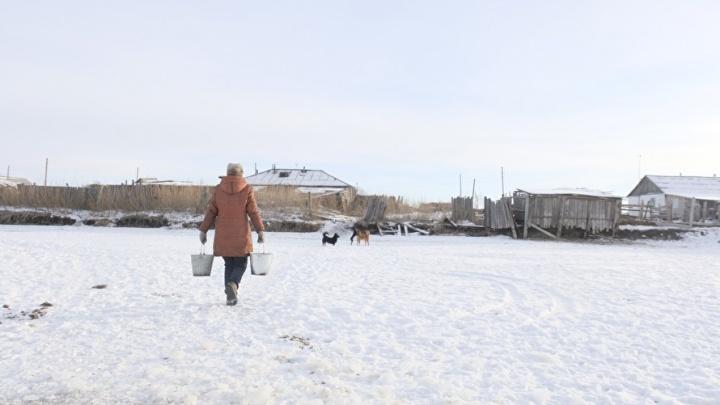 Жители поселка в Курганской области рубят лед на пруду, чтобы получить питьевую воду