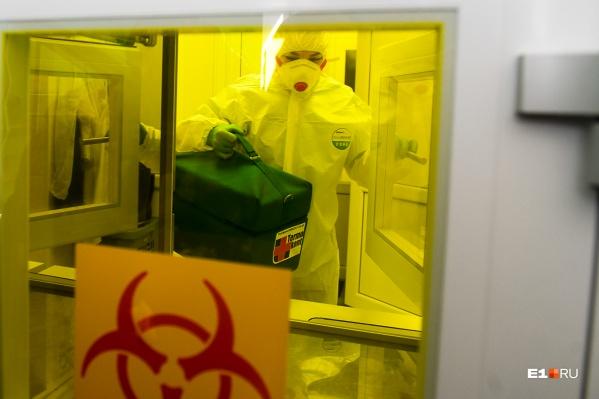 Медики надевают защитные костюмы, чтобы лечить пациентов
