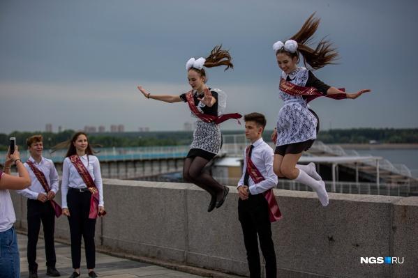 Счастливые выпускники фотографируются на набережной. И чего только не придумаешь ради фото