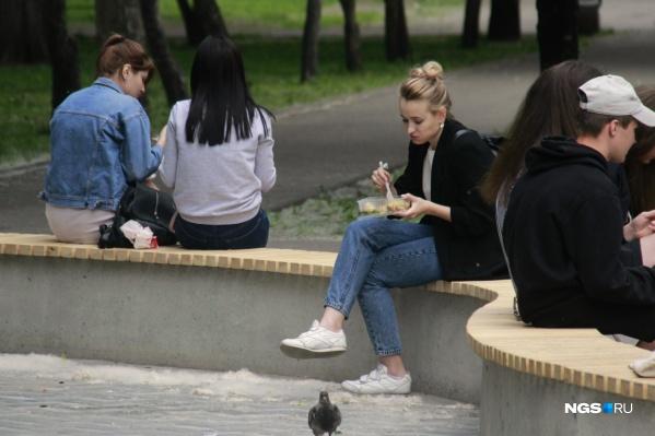 Выгнанные из ресторанного дворика горожане едят теперь на окрестных лавочках