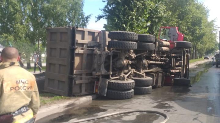 Водитель грузовика с асфальтом выехал на встречку, врезался в бордюр и уронил автомобиль на бок